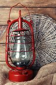 picture of kerosene lamp  - Kerosene lamp with wicker mat and burlap cloth on wooden planks background - JPG