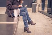 image of ordinary woman  - Detail of a young woman working with her tablet in the city streets - JPG
