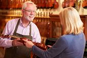 stock photo of leaving  - Customer Leaving Violin For Repair In Shop - JPG