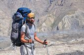 picture of shan  - Hiker with large backpack on Engilchek glacier with scenic Tian Shan mountain range in Kyrgyzstan - JPG