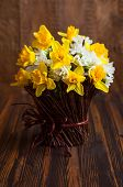 pic of daffodils  - Daffodils in a twig vase on the wooden table - JPG