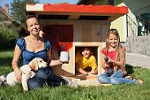 foto of labrador  - Happy kids painting the doghouse to shelter their new labrador puppy - JPG