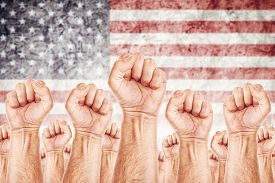 stock photo of labourer  - United States of America Labour movement workers union strike concept with male fists raised in the air fighting for their rights American national flag in out of focus background - JPG