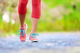 picture of jogger  - Jogging woman with athletic legs and running shoes - JPG