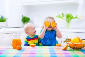stock photo of little sister  - Cute funny little girl and adorable baby boy drinking freshly squeezed orange juice for healthy breakfast in a white kitchen with window on a sunny summer morning