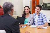foto of showrooms  - Smiling couple talking with a car dealer at new car showroom - JPG