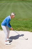 foto of take off clothes  - Female golfer taking a shot on a sunny day at the golf course - JPG