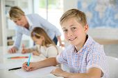 image of classroom  - Young smiling schoolboy in classroom - JPG
