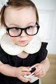 foto of lurex  - Portrait of serious little girl in black dress and glasses with mobile phone in hands - JPG