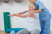 stock photo of senior class  - Instructor assisting senior woman to exercise in gym - JPG