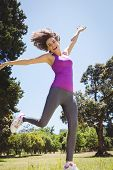 foto of leaping  - Fit woman leaping in the park on a sunny day - JPG