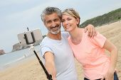 stock photo of extend  - Couple taking picture with smartphone and extendable monopod - JPG