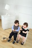 pic of lurex  - Two little child sitting on white chairs - JPG