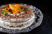 stock photo of sponge-cake  - Sponge cake with sour cream decorated with slices of orange tangerine cranberry green leaves and chocolate chips on a black background - JPG