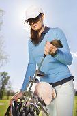foto of golf bag  - Female golf player taking golf club from bag on a summer day - JPG