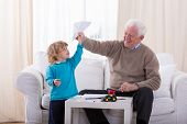 stock photo of grandpa  - Grandpa and little boy playing with paper airplane - JPG