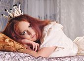 stock photo of princess crown  - Beautiful woman with white crown on her head with red long hair lying like princess and looking at camera - JPG