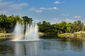 stock photo of fountain grass  - Fountain with rainbow in the artificial pond - JPG