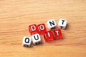 picture of dice  - Dont Quit Do It written on red and white dices on wooden background - JPG