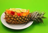 pic of green papaya salad  - Thai style fruit salad inside a pineapple with a green background - JPG