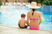 picture of swimming pool family  - Rear view of mother and son sitting on the edge of the swimming pool - JPG