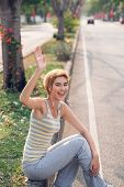 stock photo of waving hands  - Happy sporty woman sitting on the roadside and waving with her hand - JPG