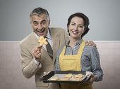 pic of gingerbread man  - Vintage woman serving home made gingerbread men cookies to her smiling husband - JPG
