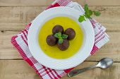 stock photo of gulab  - gulab jamun in sugar syrup in a dish on a red linen - JPG