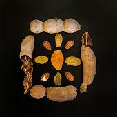 image of tamarind  - Tamarind raisins and almond on black background - JPG