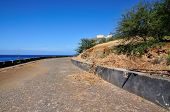 stock photo of cobblestone  - Guard rail protects a cobblestone road over the oceanfront of Sao Filipe on the island of Fog Cabo Verde - JPG