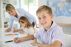 pic of schoolboys  - Young smiling schoolboy in classroom - JPG