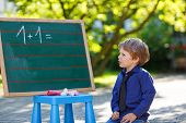 Little Boy At Blackboard Practicing Mathematics poster