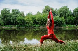 foto of virabhadrasana  - Beautiful young woman performing yoga exercises on the lake - JPG