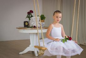 picture of fairy tail  - Portrait of little cute ballerina on swing with rose. Princess concept. Fairy tail